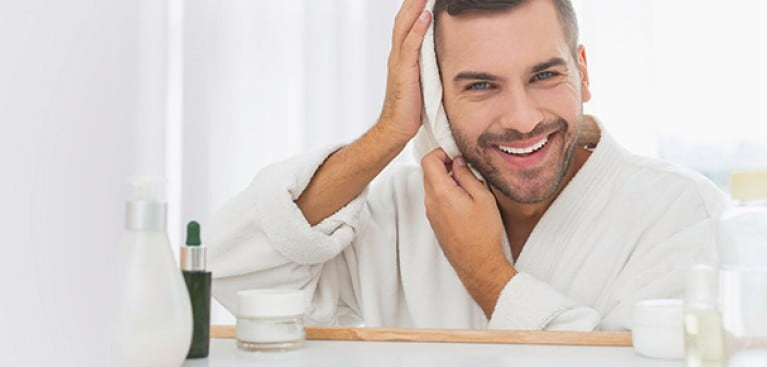 Guy drying hair with towel in mirror