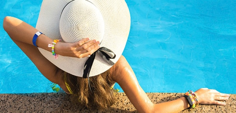 Women lounging poolside with sunhat
