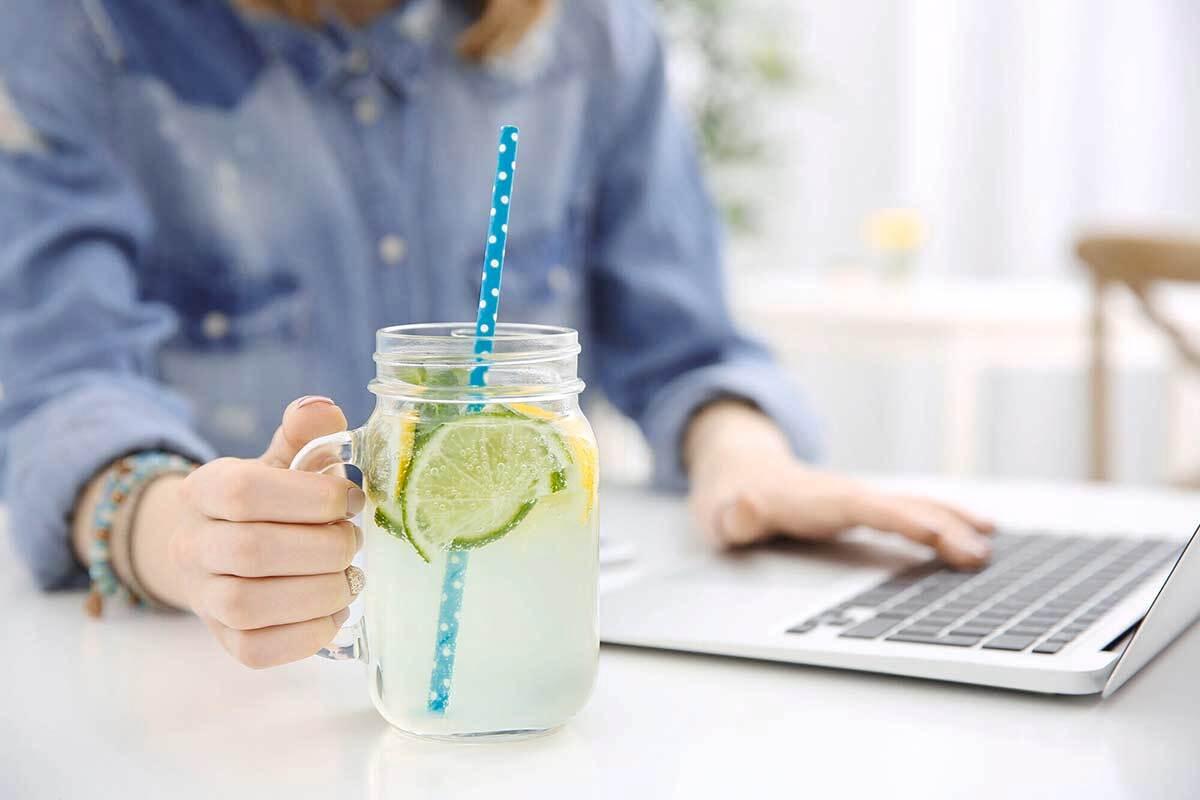 Seorang wanita tengah bekerja dengan laptopnya sambil menikmati infused water