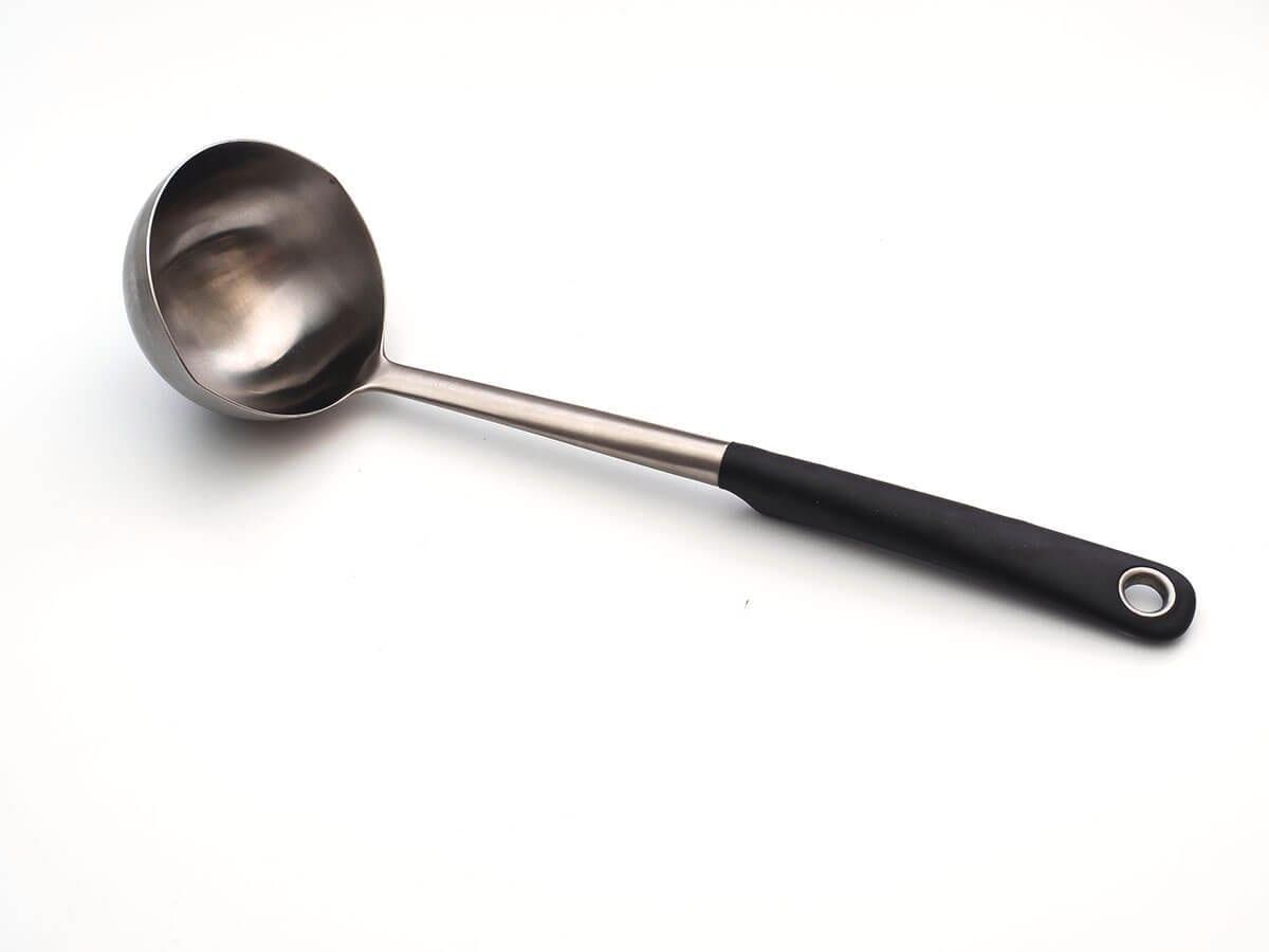 Satu sendok sayur terbuat dari logam dengan gagang hitam di atas meja transparan