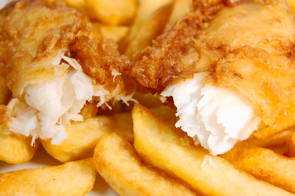 Ikan dori goreng dibelah dua dan disajikan dengan kentang goreng