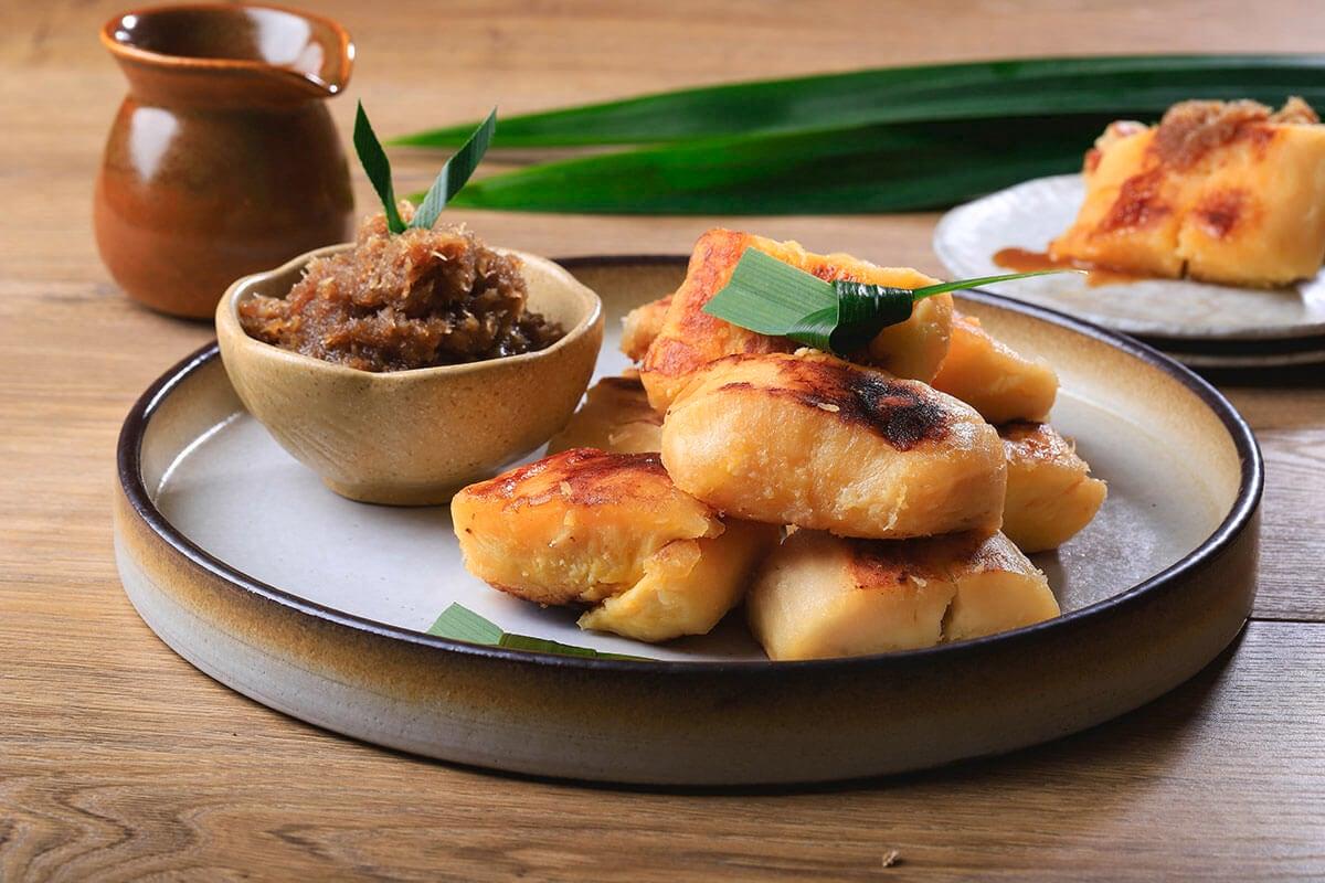 Colenak berhias daun pandan disajikan di piring dengan cocolannya di mangkuk kecil