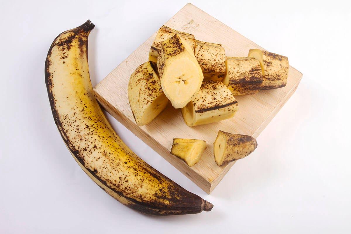 Sebuah pisang  tanduk dan potongan pisang tanduk di atas talenan kayu