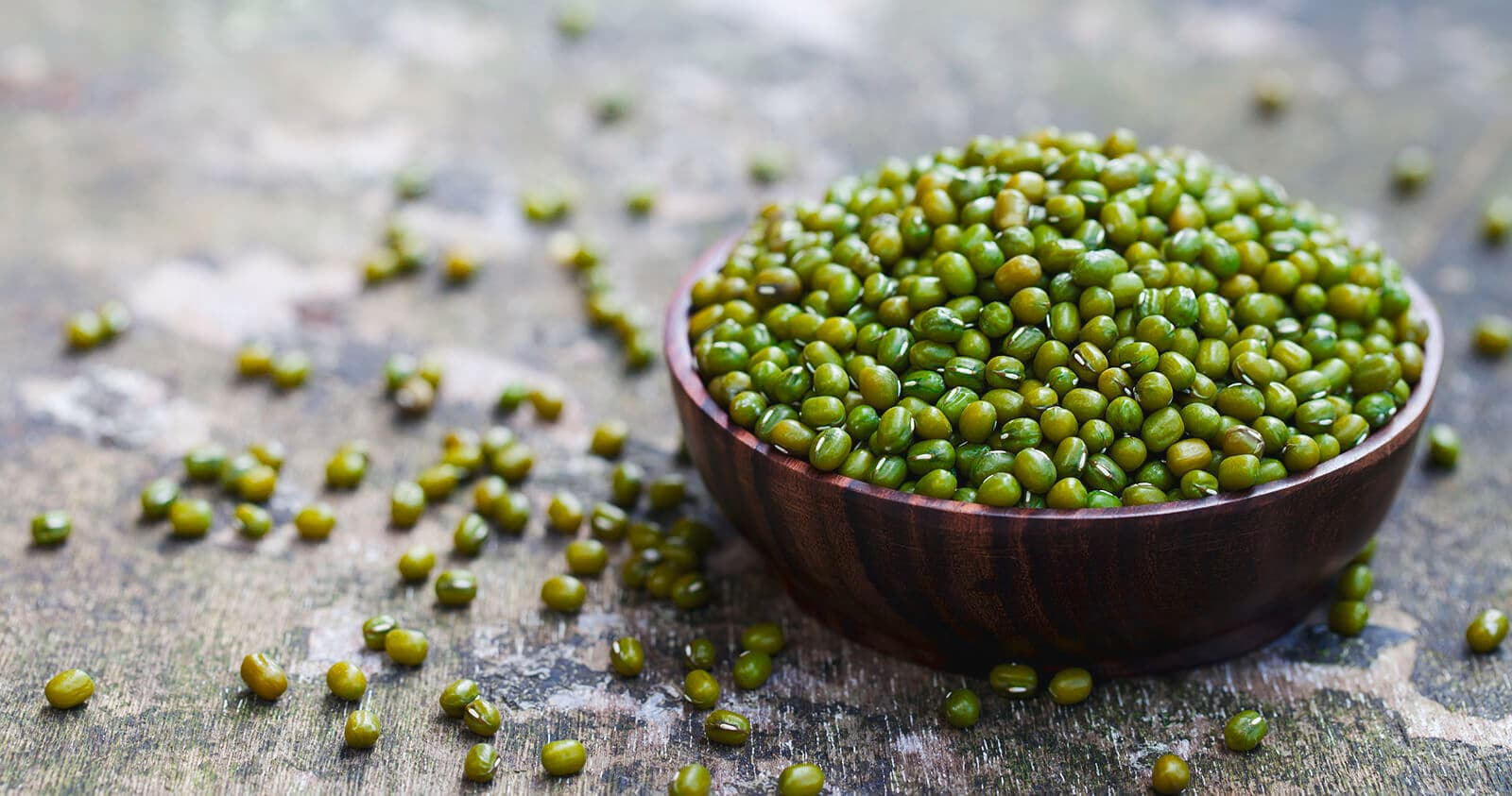 Mangkuk hitam berisi banyak kacang hijau dan dikeliling kacang yang berserakan