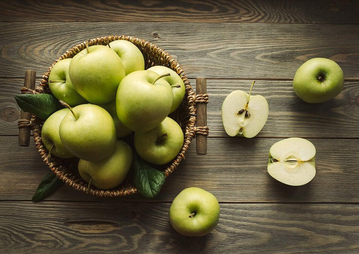 Beberapa apel hijau dalam keranjang rotan, dan potongan apel di sekitarnya