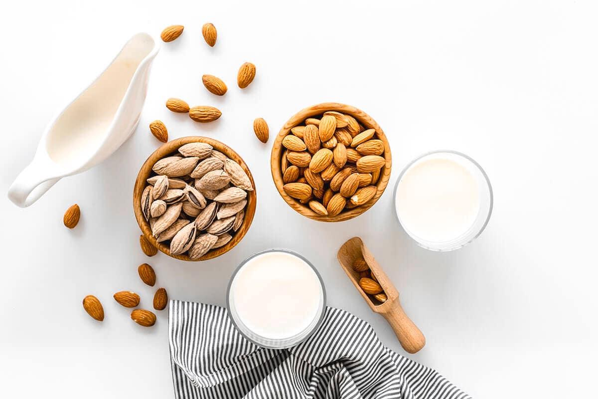 Kacang almond dalam mangkuk cokelat dan susu almond di sampingnya
