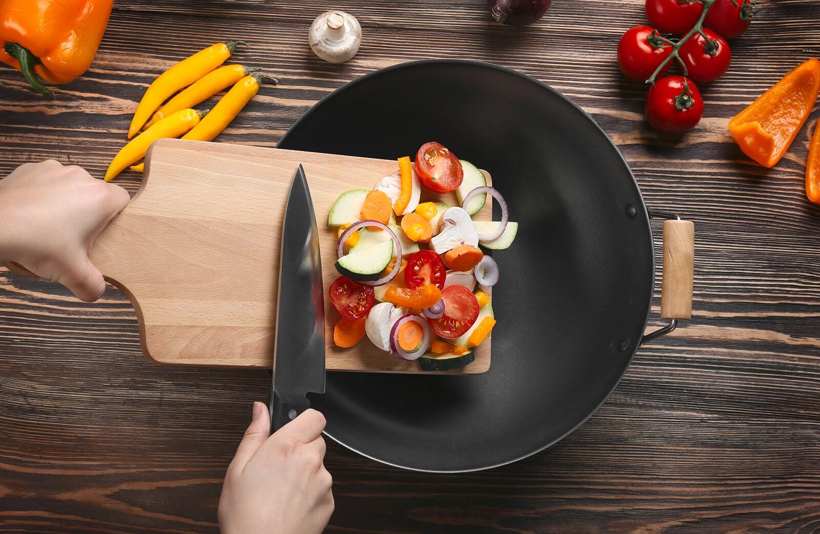 Seorang perempuan memasukkan potongan bawang dan tomat dari talenan ke dalam wajan