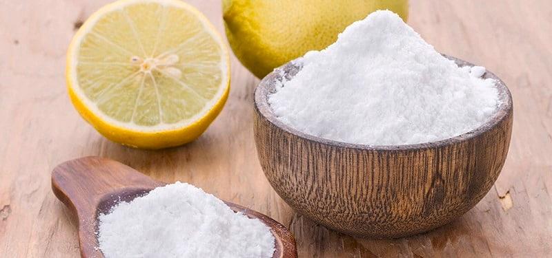 Baking soda dalam mangkuk kecil kayu dengan irisan lemon di belakangnya