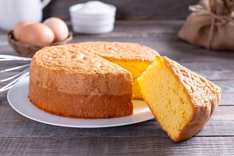 Kue bolu klasik di atas piring putih, dengan bahan-bahan kue di belakangnya