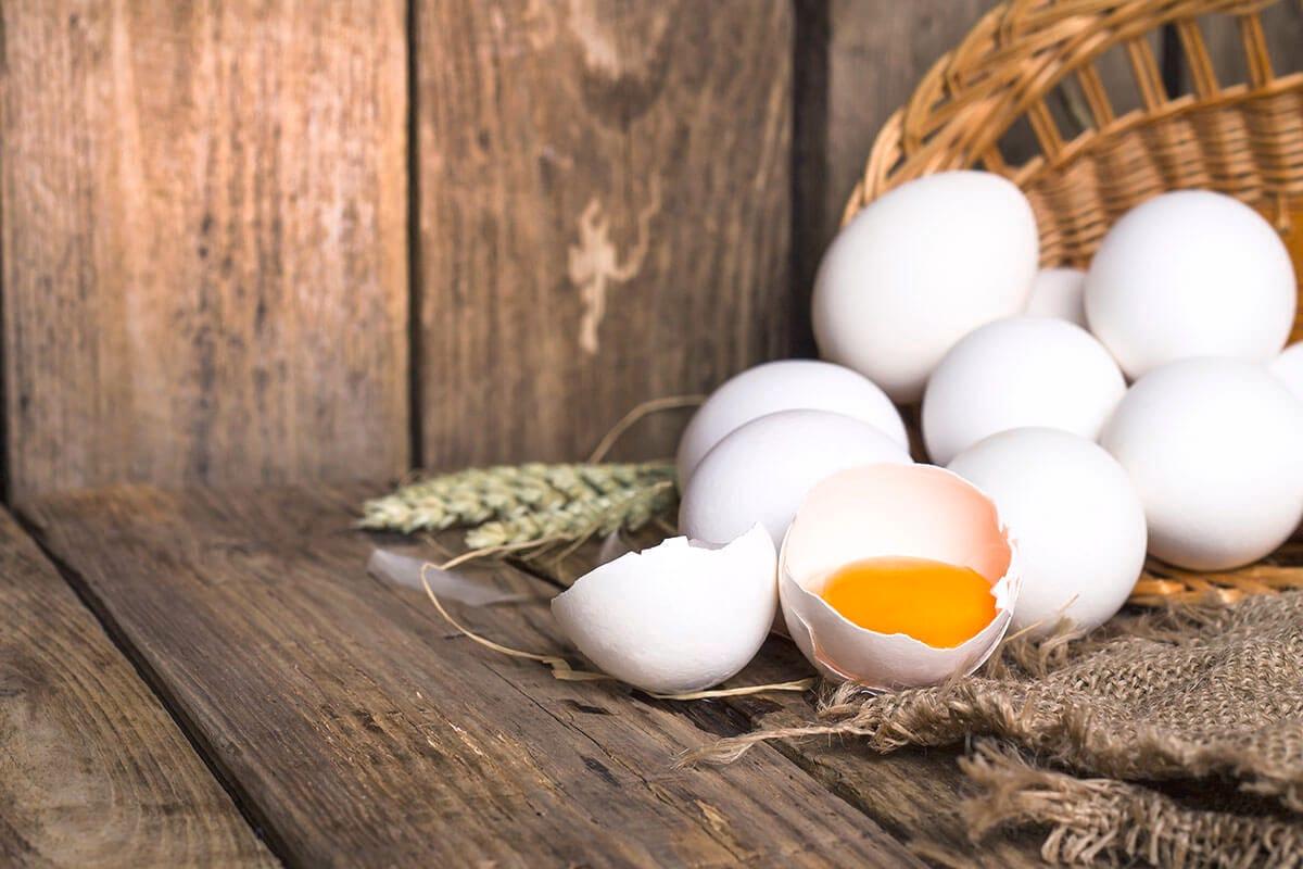 Butiran telur ayam kampung di keranjang cokelat di atas meja kayu