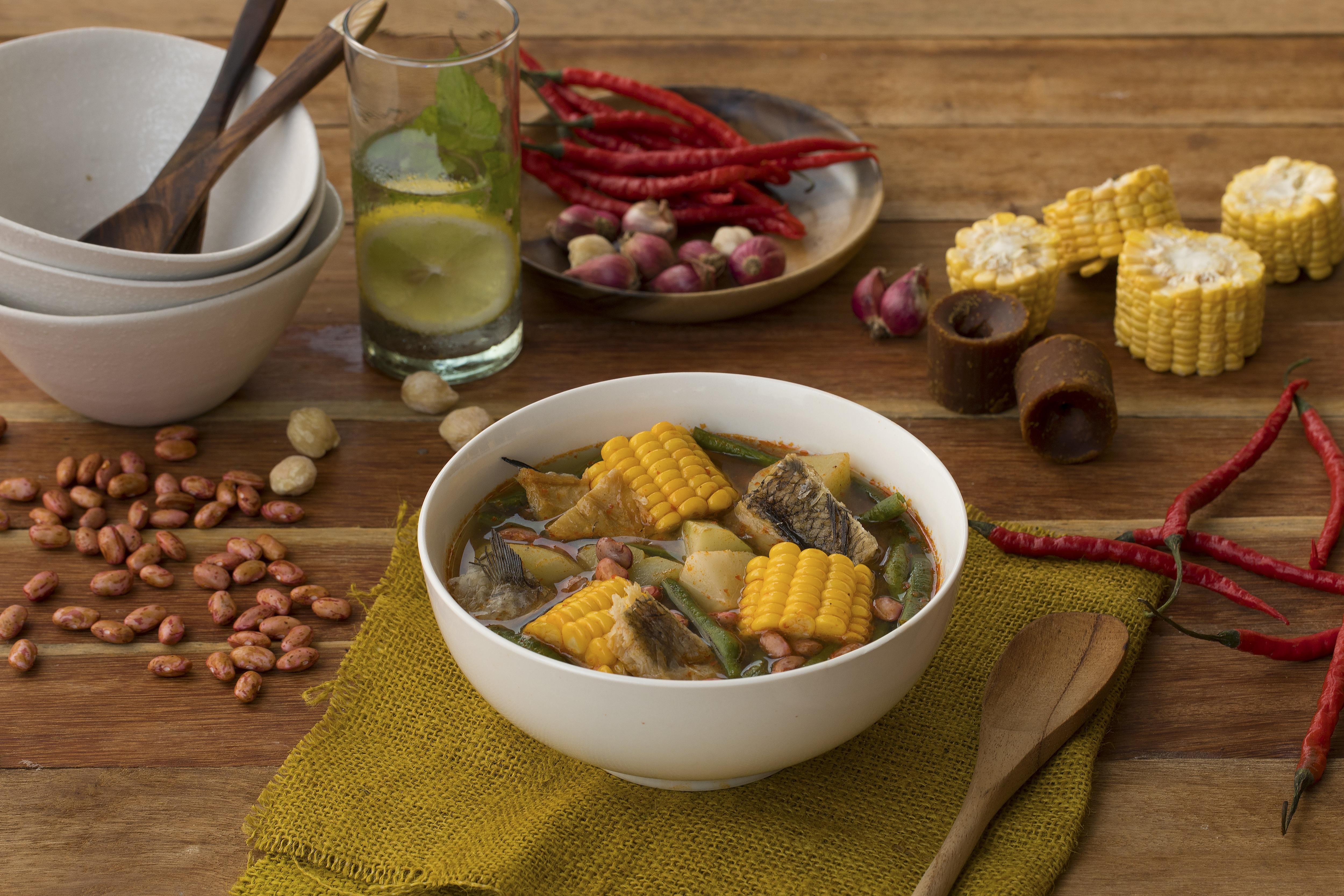 Mangkuk berisi sayur asam lengkap dengan topping berupa jagung dan sayuran.