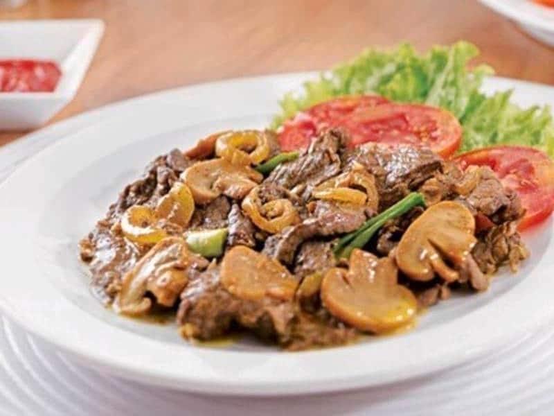 Tumis daging sapi dengan jamur disajikan di atas piring putih bersama sayuran