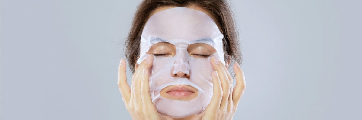Face care and beauty treatments. Woman with a cloth moisturising mask on her face isolated on gray background.