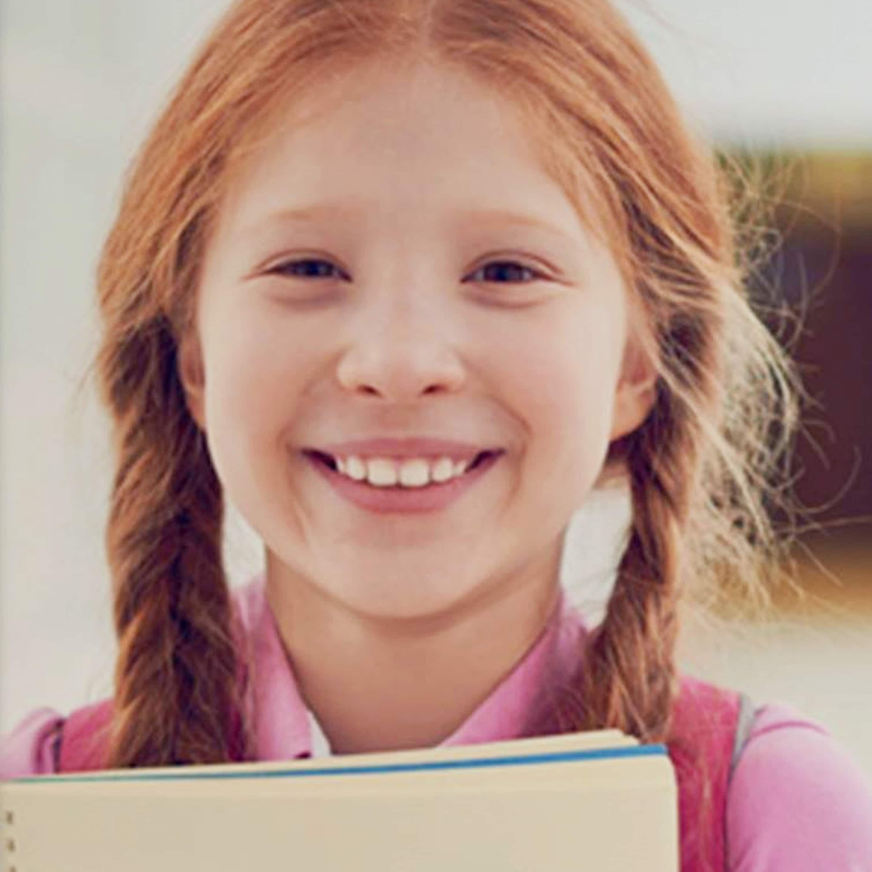 Young girl smiling at the camera holding school books