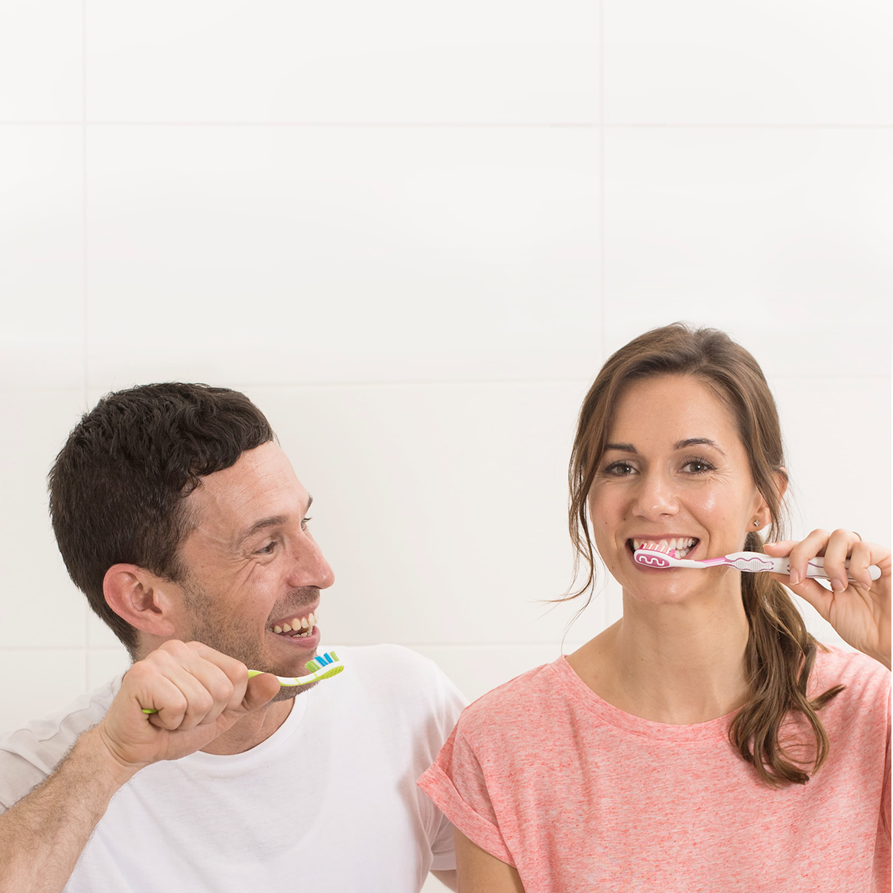 Couple smiling and brushing their teeth