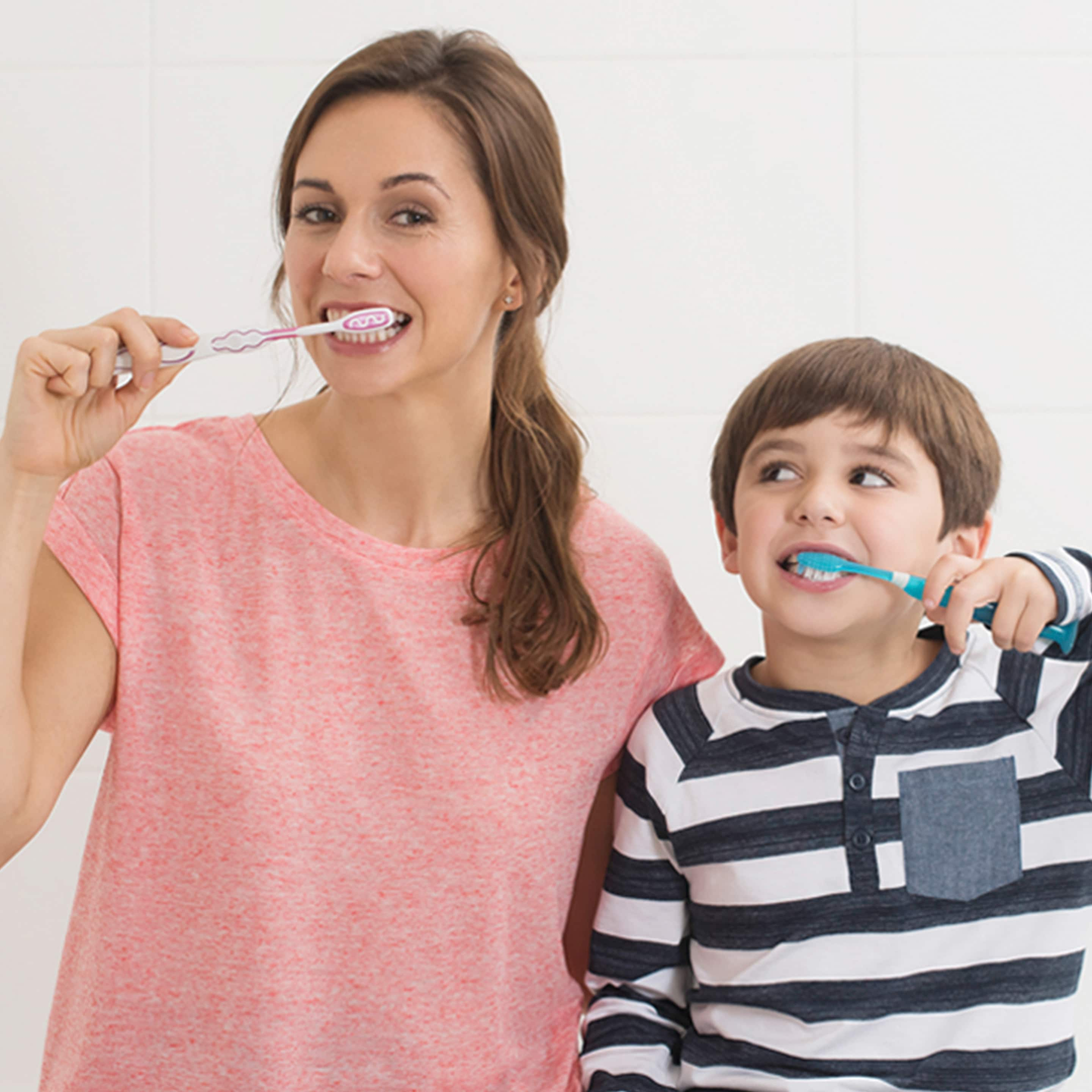 Mom and son brushing their teeth and smiling