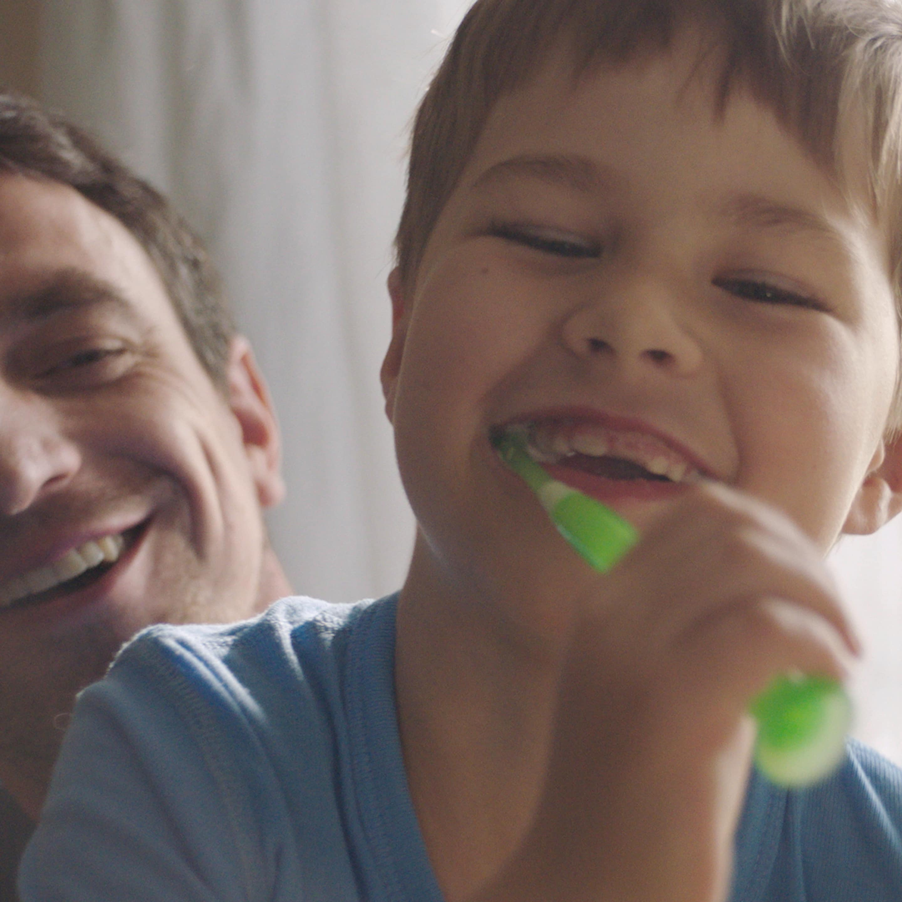 Smiling kid brushing his teeth with an electric toothbrush with his dad