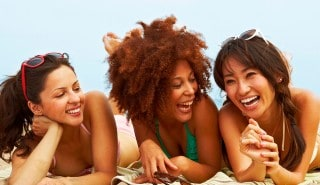 a group of woman on a beach smiling and having fun