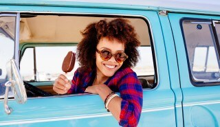 Brunette model with curly hair inside a blue car to illustrate the page of the line Keraforce Chemistry, Silk.