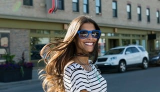 Happy woman with smooth long hair, wearing blue sunglasses and crossing the street.