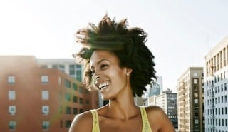 Model with black curly hair, smiling and with yellow blouse to illustrate the page of the complete Silk Hair Regeneration line.