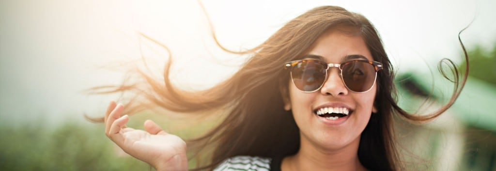 A smiling woman wearing sunglasses, her wavy black hair blowing gently in the wind.