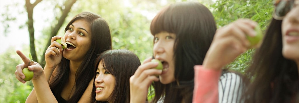 Four women, all with thick black hair, eating apples and pointing towards something in the distance.
