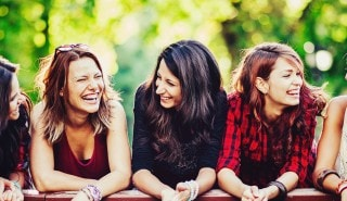 A group of girlfriends with straight and curly hair laughing together on a bridge by a lake.