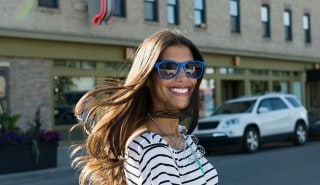 Smiling model with thick brown hair, wearing blue sunglasses and smiling as she crosses the street.