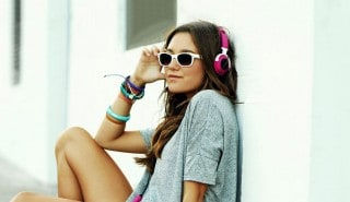 A girl wearing pink headphones and white sunglasses relaxeing against a wall.