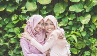 Two woman wearing hijabs, hugging each other