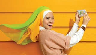 A young woman wearing a hijab taking a selfie with a cellphone and smiling