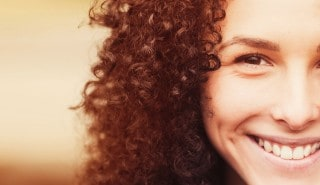 A girl smiling with curly hair