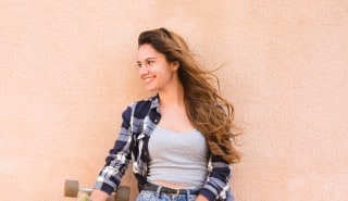 A girl leaning against a wall and the breeze moves her wavy hair