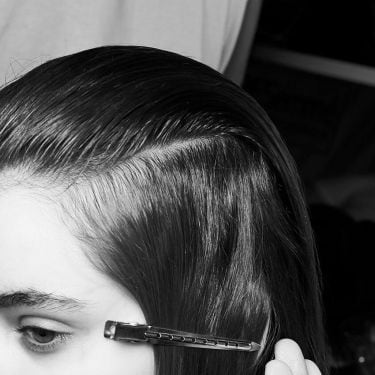 A model's head with her hair brushed to the side.