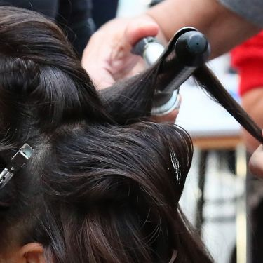 Two stylists use a brush and a hair dryer to style a woman's hair.