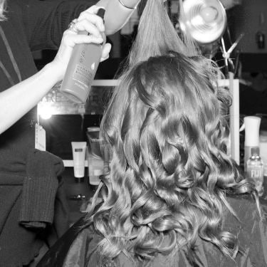 A model with curly hair getting her hair set by a stylist.