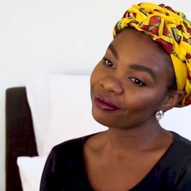 Blogger wearing a black top and yellow, print head wrap with a white bedroom background