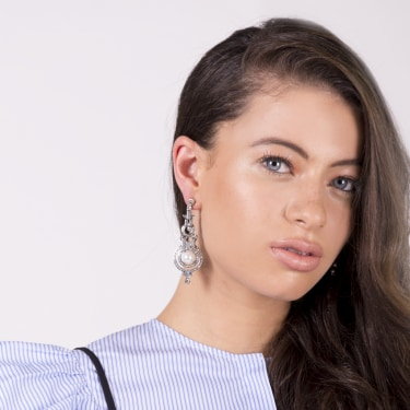 Model with blue ruffle shirt, long brown hair, blue eyes and silver hanging earrings with pearl.