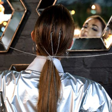 A model with her hair in a loose braid, with a stylist straightening her hair with irons