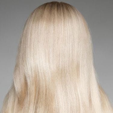 Portrait Of Beautiful Young Blonde Woman With Long Wavy Hair. Back view
