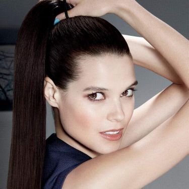 A woman tying her hair into a high ponytail whilst looking directly into the camera.