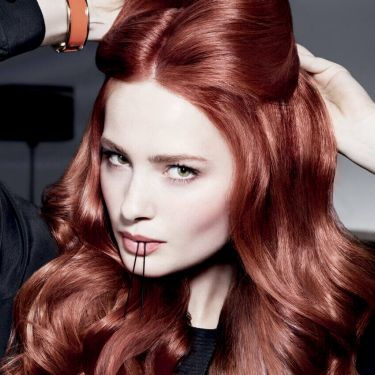 A woman holding a bobby pin in her mouth as she puts her red hair up and looks direct to camera.