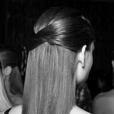 A model with the side sections of her hair gathered around the back of her head frizz-free.