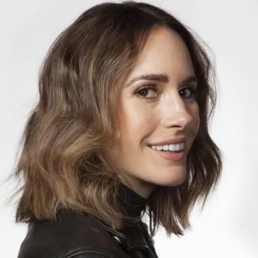 Louise Roe smiling at the camera, wearing a black leather biker jacket