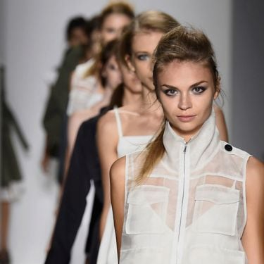 A line of models on the runway with a model wearing a white sleeveless jacket with pockets