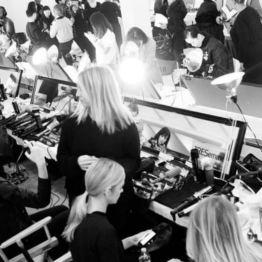 Models sitting in front of mirrors with hairstylists, photographers, styling tools and hair products.