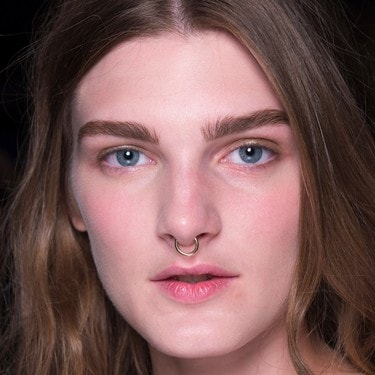 A model with long, wavy brown hair, thick eyebrows and a nose ring