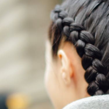 A model with dark brown hair in two thick braids