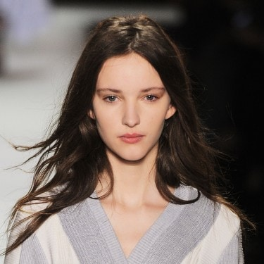 A model on the runway, with long dark brown hair, wearing a grey and white V-neck top.